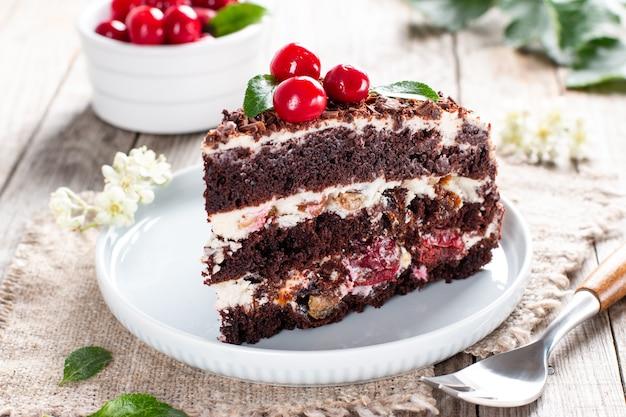 Un pezzo di torta al cioccolato con ciliegia sul piatto su un tavolo di legno