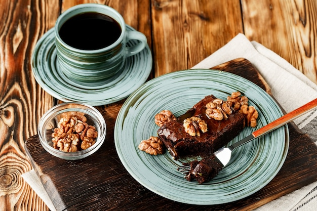 Pezzo di torta al cioccolato con noci sul piatto verde