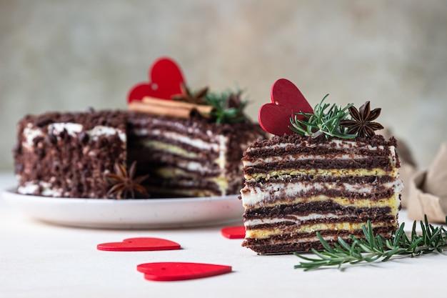 Il pezzo di torta al cioccolato a strati e cuori rossi