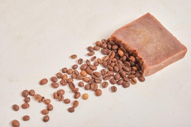 Pezzo di cacao sapone fatto in casa e chicchi di caffè, sfondo beige copia sapce