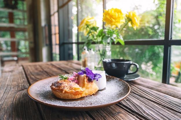 Un pezzo di torta al cocco con una bella decorazione e una tazza di caffè sul tavolo di legno