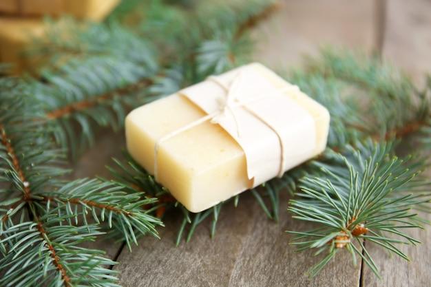 Pezzo di sapone di conifere e rami su fondo di legno, vista ravvicinata