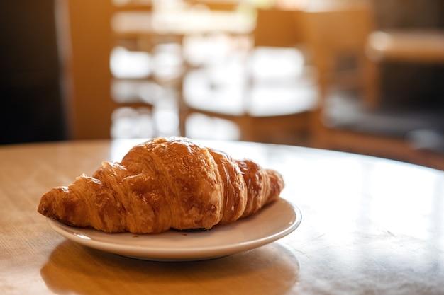 Un pezzo di croissant su un piatto bianco sulla tavola di legno nella caffetteria