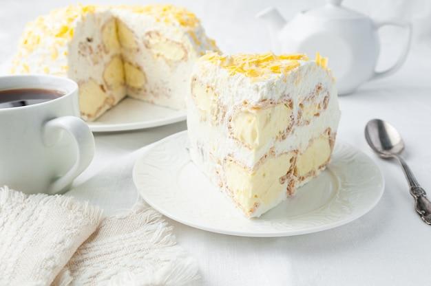 Un pezzo di torta alla crema con panna montata decorato con gocce di cioccolato giallo fatto in casa su un piatto bianco vicino a un cucchiaio e una tazza sullo sfondo c'è un piatto con una torta e una teiera bianca