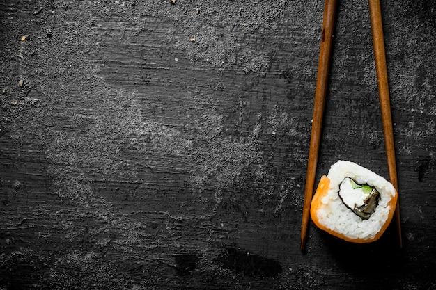 Pezzo di delizioso sushi giapponese rotoli con bastoni sul tavolo rustico nero