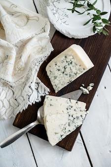 Un pezzo di formaggio blu dor su un tagliere di formaggi con formaggi erborinati delicatezza coltelli.