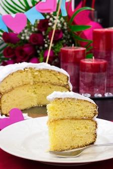 Pezzo di torta al limone festosa, candele e un grande mazzo di rose rosso scuro in background.