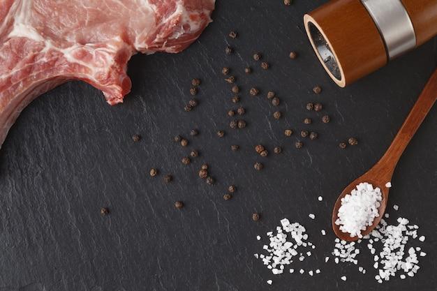 Pezzo di carne fresca su ardesia con pepe e sale