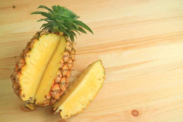 Pezzo di ananas maturo fresco tagliato da tutta la frutta su fondo in legno