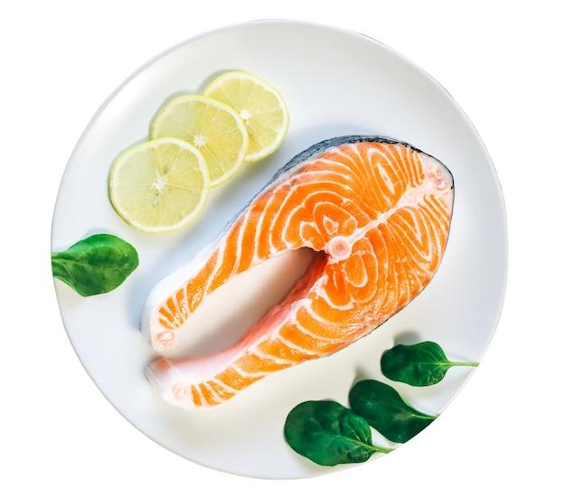 Un pezzo di salmone fresco isolato su sfondo bianco. bistecca di pesce su un piatto bianco con spinaci e limone. vitamina omega 3, stile di vita sano. cibo vegetariano naturale. vista dall'alto.