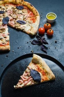 Un pezzo di pizza italiana appena sfornata su un piatto nero.