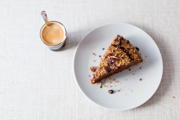 Pezzo di torta al cioccolato artigianale con noci e caffè espresso pronto a prendere