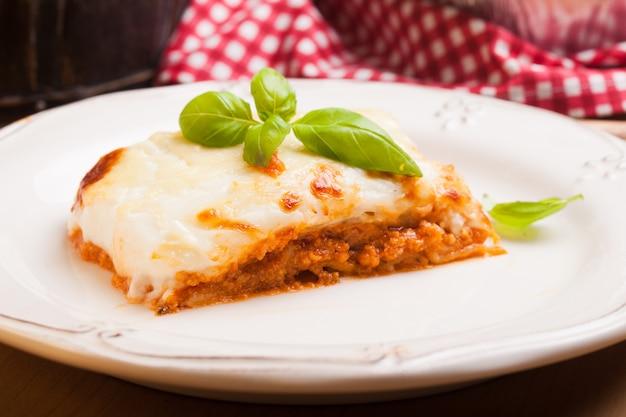Pezzo di lasagne alla bolognese con foglie di basilico in un piatto bianco
