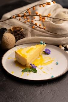 Un pezzo di cheesecake al limone guarnito con fiori e foglie di menta e salsa al limone