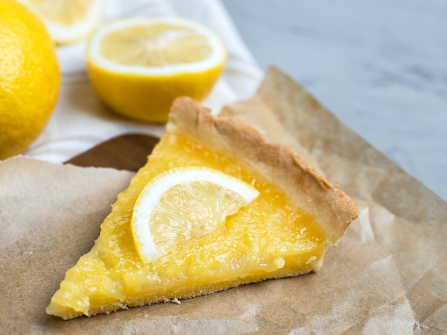 Pezzo di torta al limone con fetta di limone closeup, copia dello spazio.