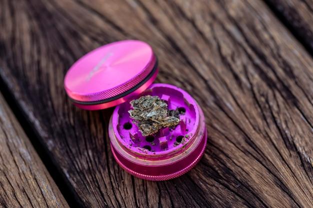 Pezzo di marijuana su macinino per erbe pronto per essere schiacciato e fumato - messa a fuoco selettiva.