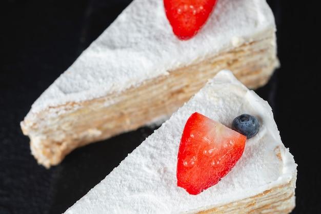 Pezzo di torta marshmallow con fragole su superficie scura dark