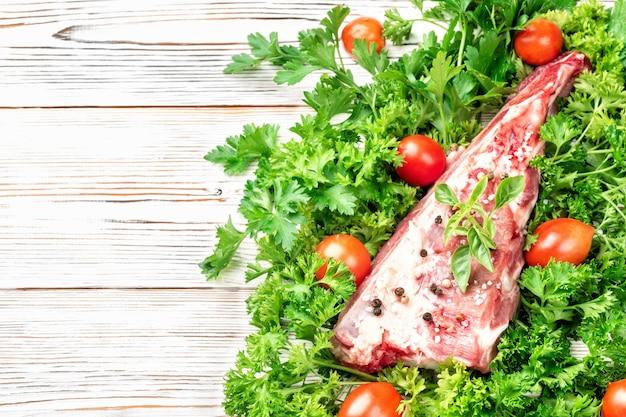 Pezzo di costoletta di carne di maiale costola spatola condita con sale e pepe e rametto di basilico
