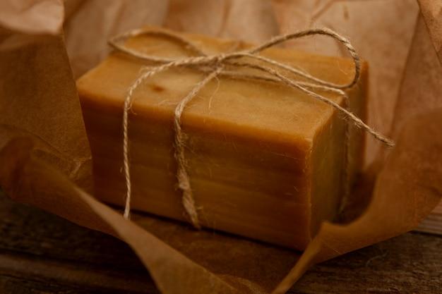 Un pezzo di sapone da bucato naturale avvolto in carta artigianale e legato con spago. avvicinamento.