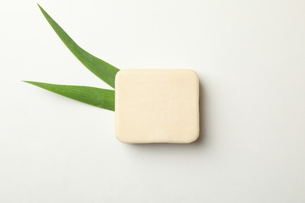 Pezzo di sapone naturale e foglie su sfondo bianco