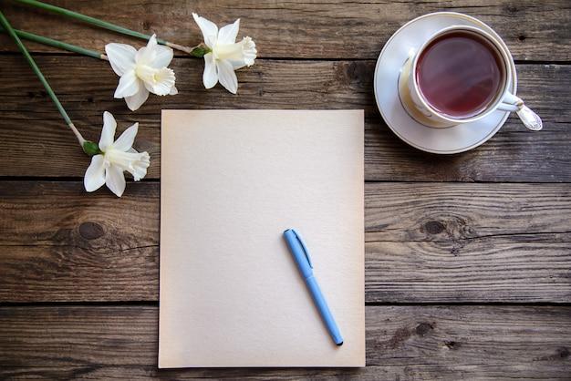 Un pezzo di carta con la penna e narcisi bianchi e una tazza di tè su fondo di legno