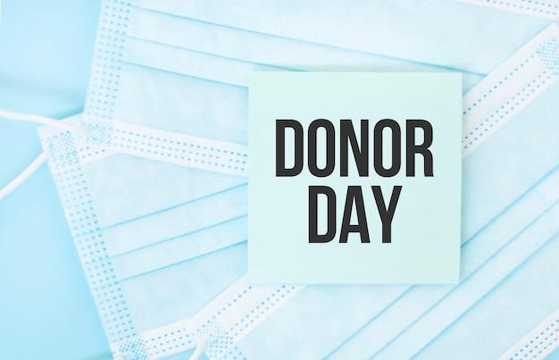 Pezzo di carta con la frase donor day sul mucchio di maschere mediche blu