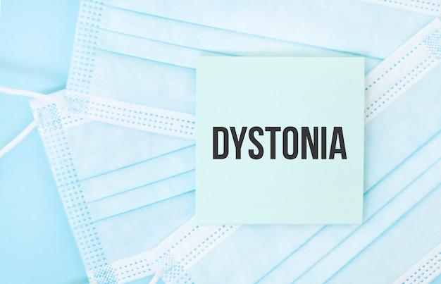 Pezzo di carta con la frase dystonia sul mucchio di maschere mediche blu. concetto di pandemia di coronavirus