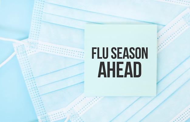 Pezzo di carta con la frase flu season ahead su un mucchio di maschere mediche blu.