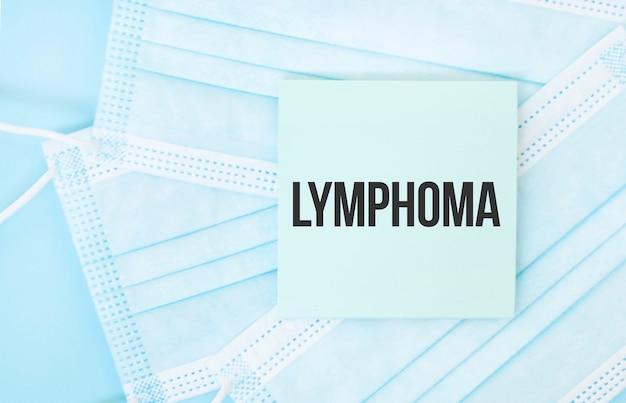 Pezzo di carta con la frase lymphoma sul mucchio di maschere mediche blu