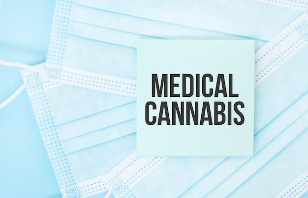 Pezzo di carta con frase medcial cannabis sul mucchio di maschere mediche blu. concetto di pandemia di coronavirus