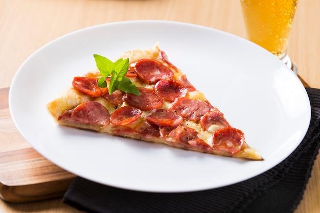 Pezzo di pizza ai peperoni sulla tavola di legno Foto Premium