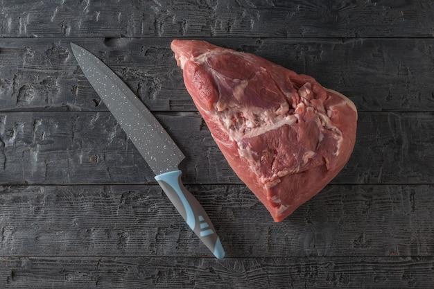 Un pezzo di maiale con un grosso coltello su un tavolo di legno nero. ingredienti per la cottura di piatti di carne. la vista dall'alto.