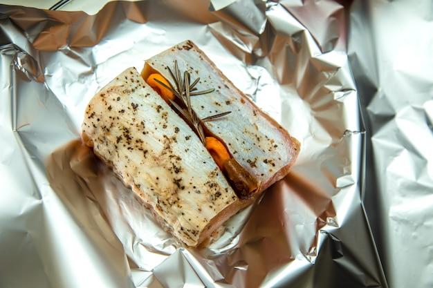 Pezzo di carne cruda al rosmarino e albicocche secche al cartoccio pronto da cuocere.