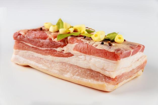 Pezzo di pancetta di maiale cruda con aglio e foglie di alloro isolato sul tavolo bianco.