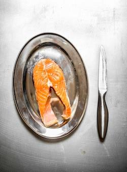 Pezzo di salmone crudo su un vassoio sul tavolo di metallo.