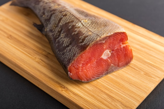 Pezzo di pesce affumicato su un tagliere. pesce da vicino
