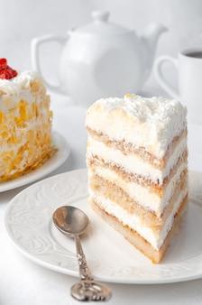 Un pezzo di pan di spagna con panna montata e frutti di bosco guarnito con pezzi di cioccolato bianco fatto in casa su un piatto bianco sullo sfondo una torta una teiera e una tazza bianca sfondo bianco