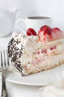 Un pezzo di pan di spagna con panna montata e frutti di bosco guarnito con pezzi di cioccolato bianco fatto in casa su un piatto bianco sullo sfondo una torta una teiera e una tazza bianca