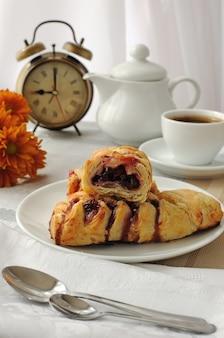 Un pezzo di strudel alle ciliegie con una tazza di caffè al mattino