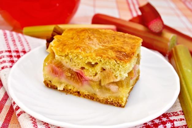 Un pezzo di torta dolce con rabarbaro, gambi di rabarbaro, cannella, composta di brocca su sfondo di tovaglia di lino