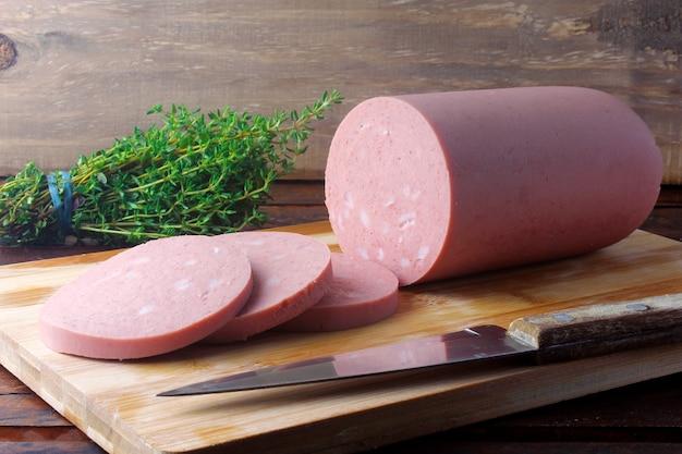 Pezzo di mortadella intera di maiale cruda sul tagliere con alcune fette. cibo italiano