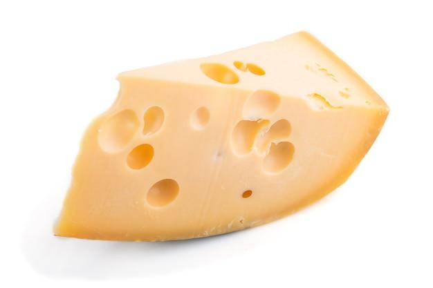 Pezzo di formaggio giallo isolato su superficie bianca