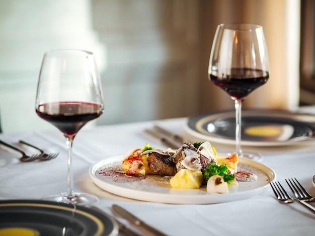 Pezzi di bistecche di carne di manzo con diverse salse e vino rosso