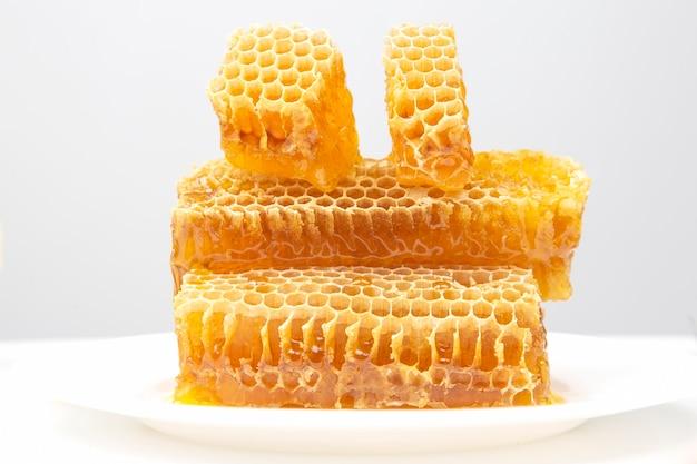Pezzi di miele di cera d'api su bianco