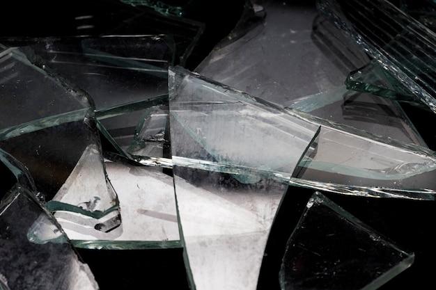 Pezzi di vetro rotto su sfondo nero. foto di alta qualità
