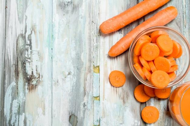 Pezzi di carote in una ciotola di vetro. su legno