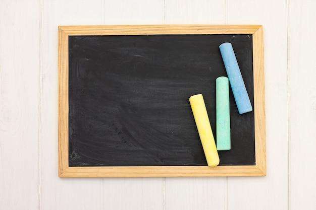Pezzi di gesso su una lavagna di scuola su un fondo di legno bianco. vista dall'alto. copia spazio.