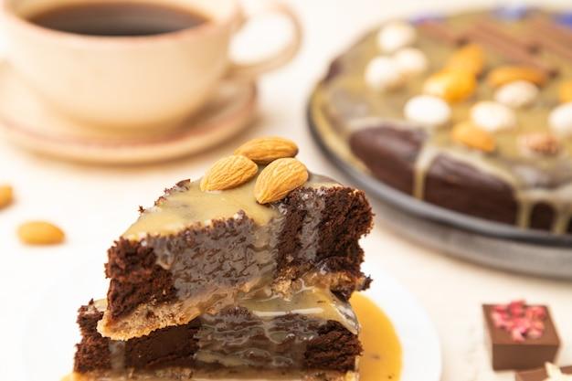 Pezzi di torta brownie al cioccolato con crema al caramello e mandorle su una superficie di cemento bianco