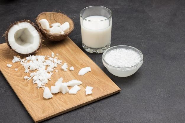 Pezzi di cocco e metà di cocco a bordo. latte di cocco in vetro e ciotola.