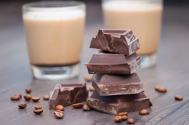 Pezzi di cioccolato fondente, chicchi di caffè e tazze di cacao o caffè con latte sulla tavola di legno.